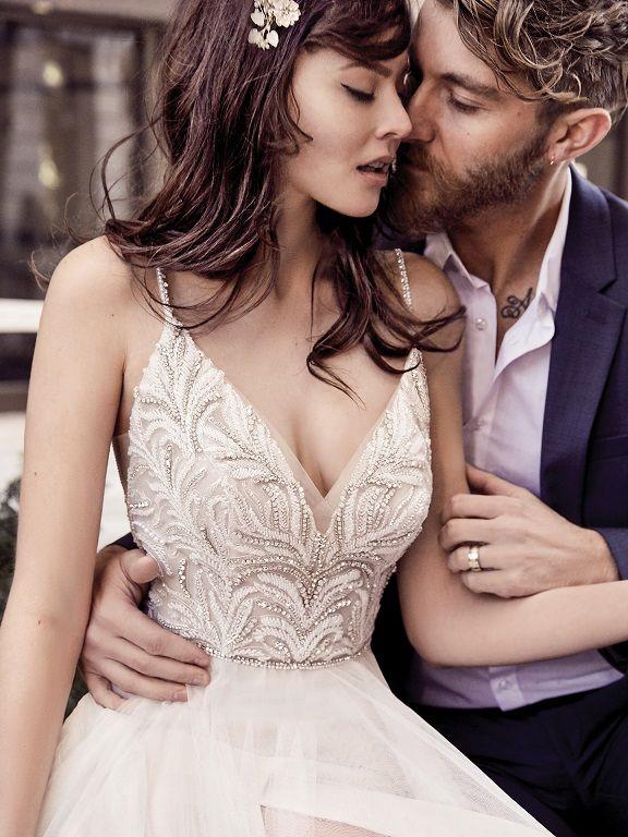 Mann in Anzug hält Frau in Maggie-Sottero-Charlene Brautkleid im Arm