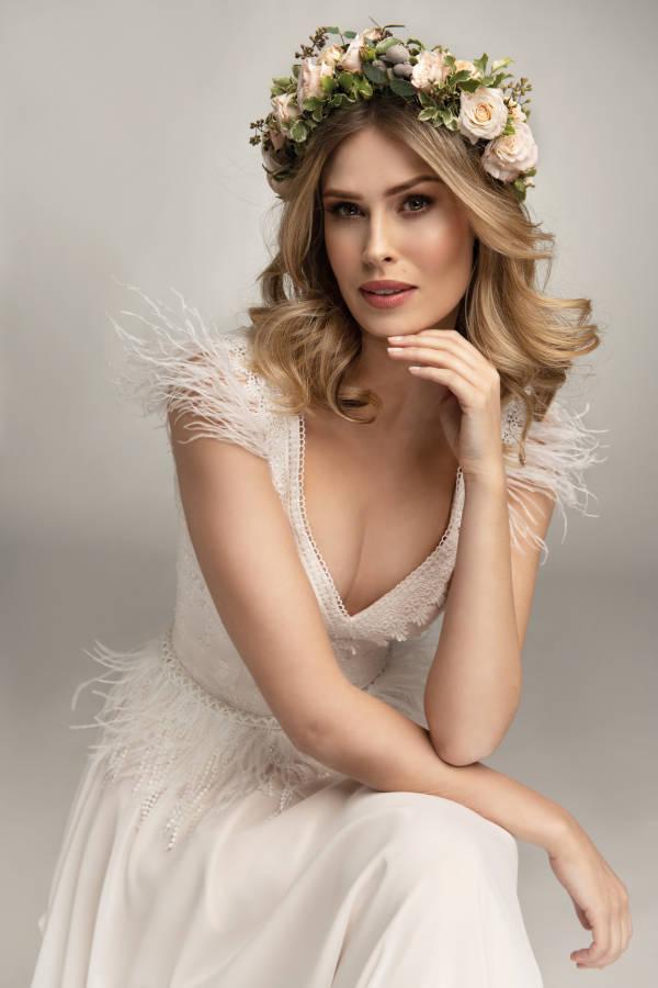 Junge blonde Frau mit Brautkleid und großem Blumenkranz