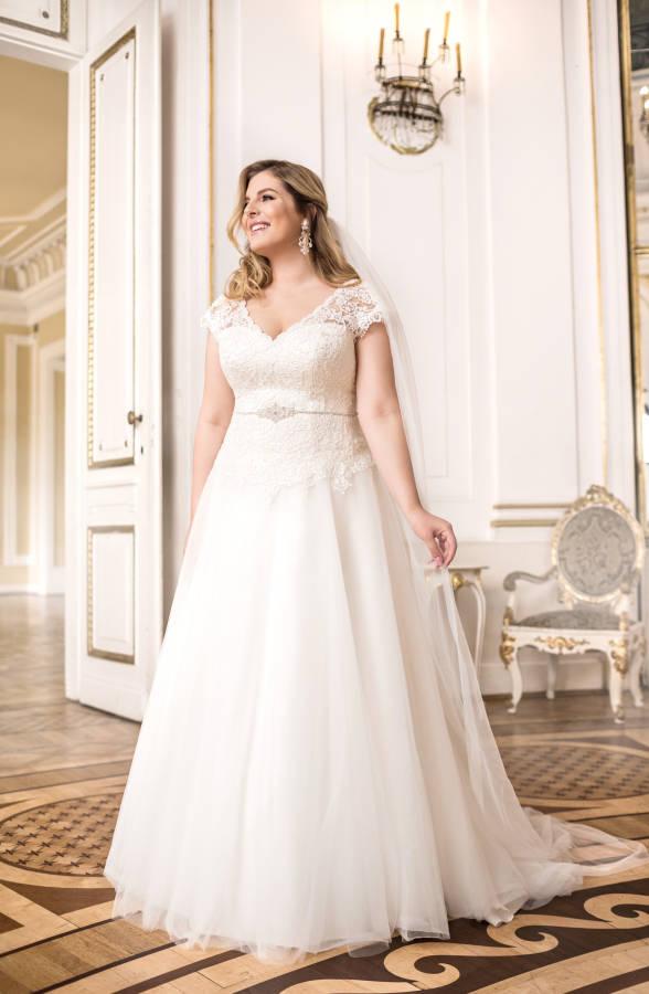 Junge blonde Frau in curvy Brautkleid mit Ärmeln und Gürtel in Saal vor großer Tür