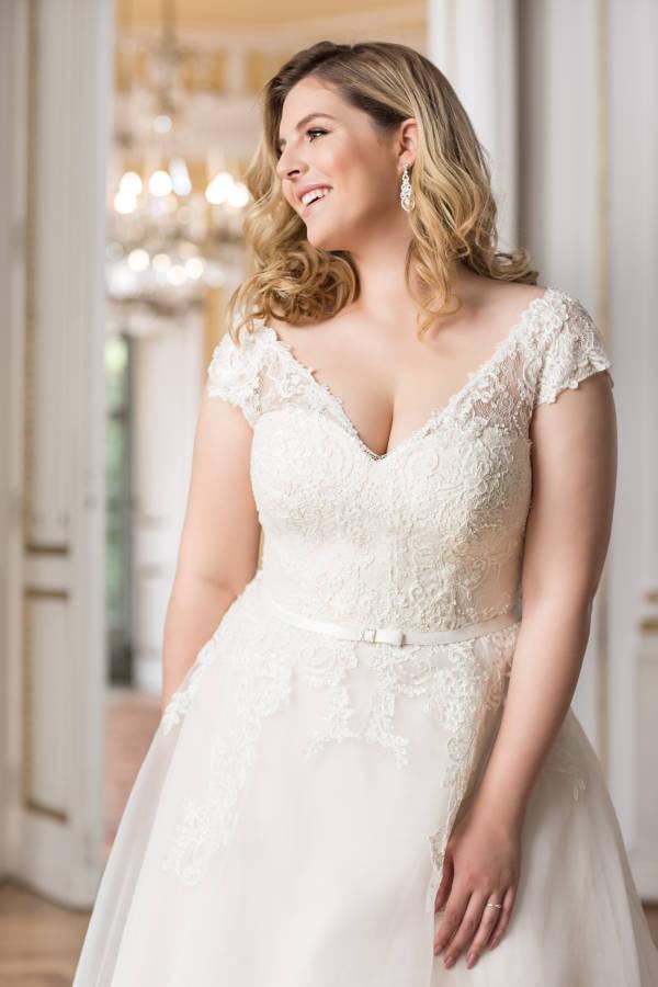 Junge blonde Frau in curvy Brautkleid mit Ärmeln und dezentem Gürtel