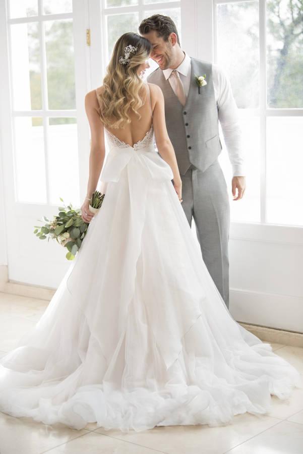 Junge Frau in Brautkleid mit tiefem Rückenausschnitt und Blumenstrauß mit Mann in Anzug lächeln