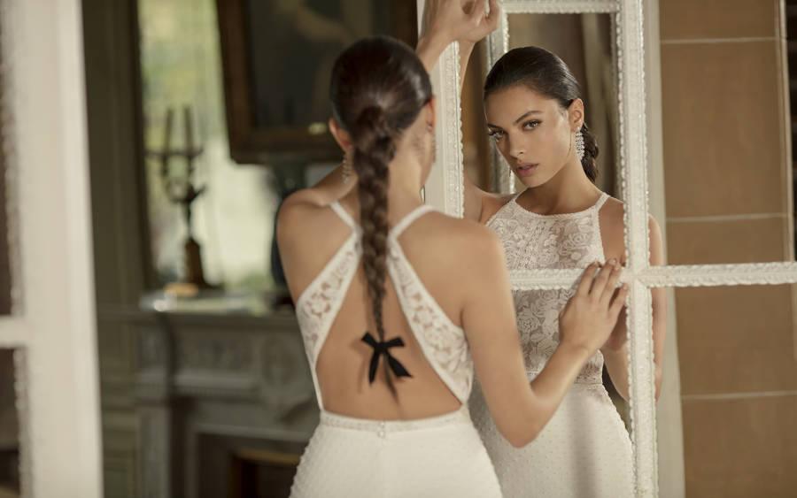 Junge Frau in engem Brautkleid mit geflochtenem Zopf und Rückenausschnitt schaut durch Spiegel