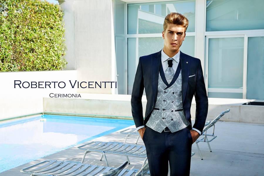 Junger Mann in Herrenmode Dolce Vita Roberto Vicentti blauer Anzug mit Krawatte neben Pool