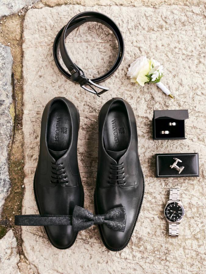 Anzugschuhe Gürtel Fliege Armbanduhr Ringe und Manschetten auf Stein