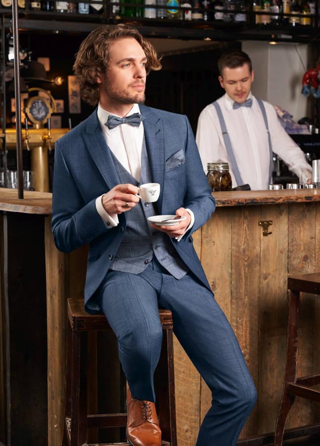 Mann mit blauem Anzug, Fliege und braunen Schuhen an Theke mit Espresso in der Hand