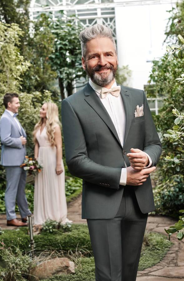 Alter Mann mit Bart und weißen Haaren in olivfarbenem Anzug lacht in die Kamera in Garten