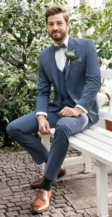 Mann mit blauem Anzug und braunen Schuhen auf weißer Bank lächelnd
