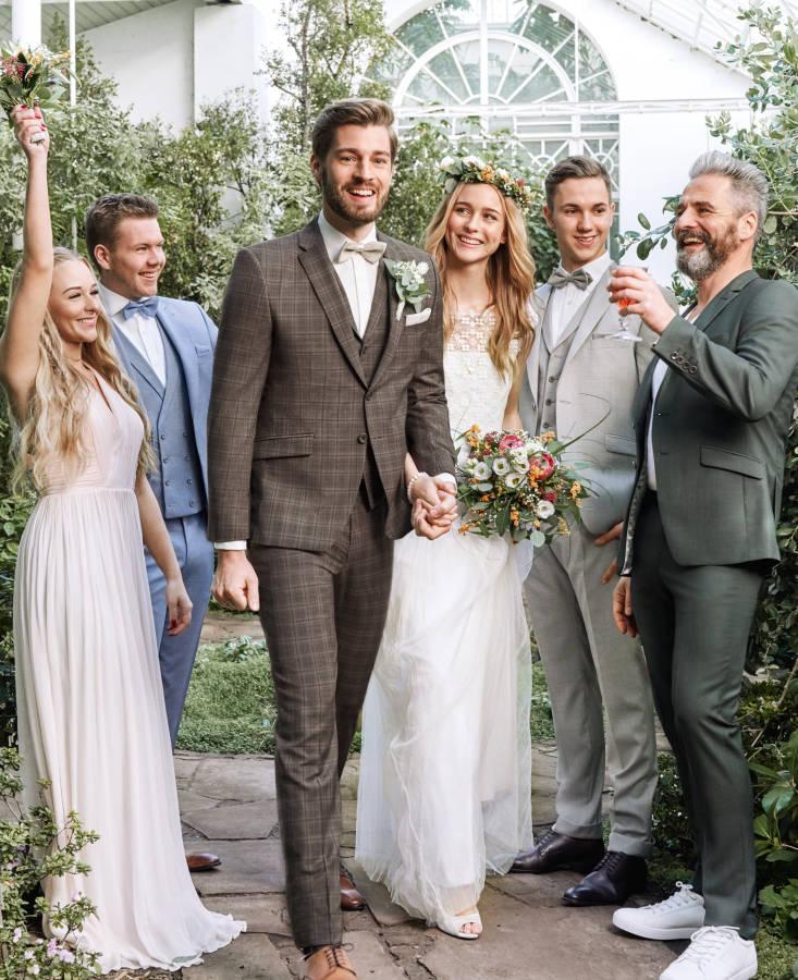 Brautpaar in braunem Anzug und schlichtem Brautkleid zwischen feiernden Angehörigen in Wintergarten lachend
