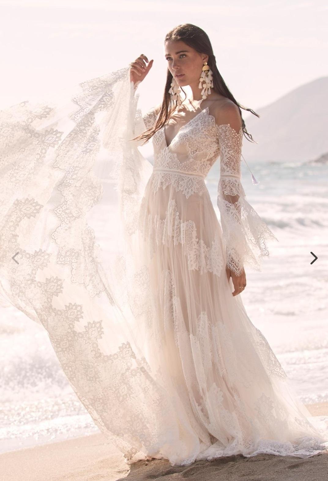 Frau trägt Boho Brautkleid mit Trompetenärmeln am Strand